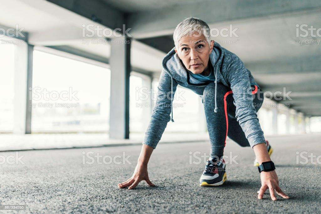 Female runner training in starting position stock photo