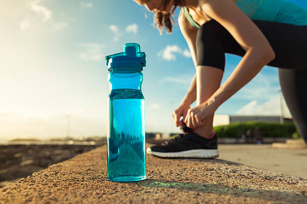 female runner tying her shoes next to bottle of water - drinking water stock photos and pictures