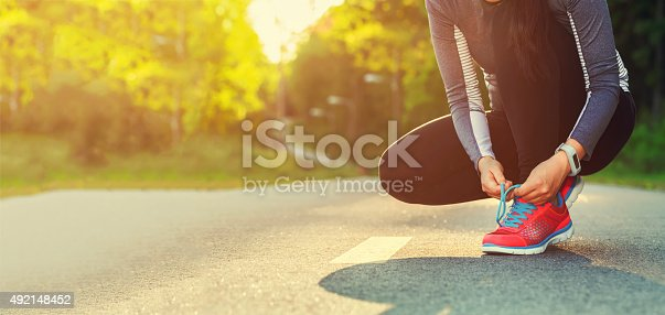 istock Female runner tying her shoes preparing for a jog 492148452