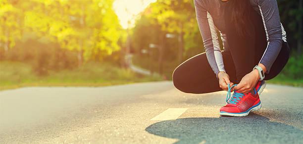 weibliche läufer binden ihre schuhe vorbereitung auf einen lauf - joggerin stock-fotos und bilder