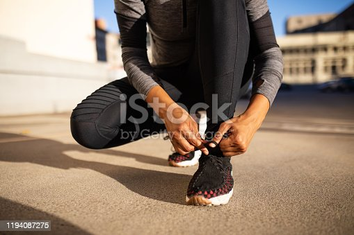 Close up of sporty woman tying shoelace while kneeling outdoors. Woman tying shoelace on running shoes before practice.