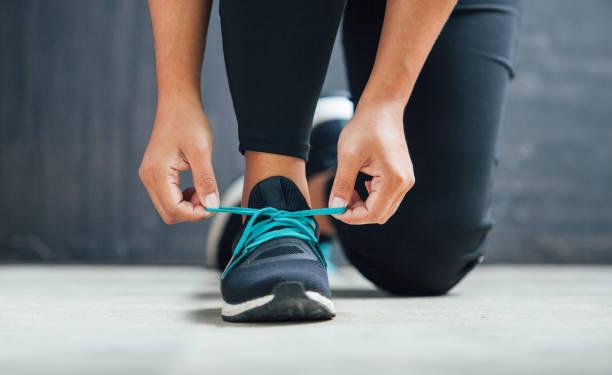 kobieta biegaczka wiązana buty przygotowuje się do biegu - but sportowy zdjęcia i obrazy z banku zdjęć