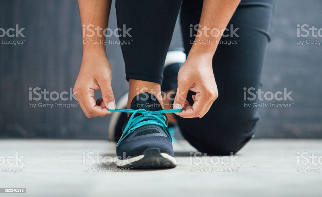 Female runner tying her shoes preparing for a run stock photo