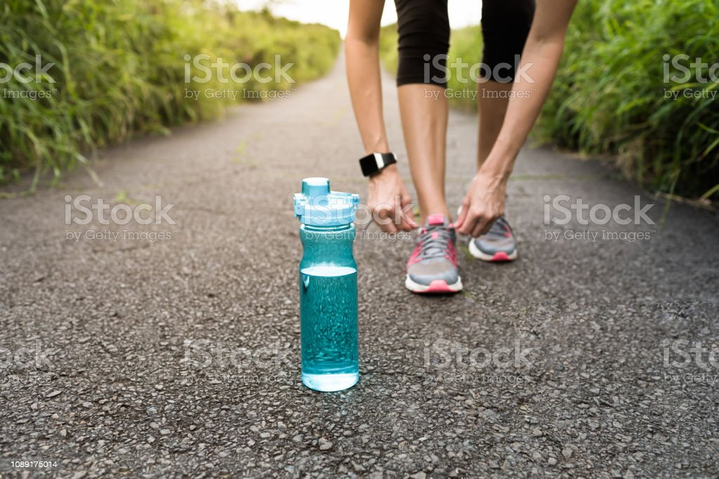 Female runner tying shoe next to water bottle. stock photo