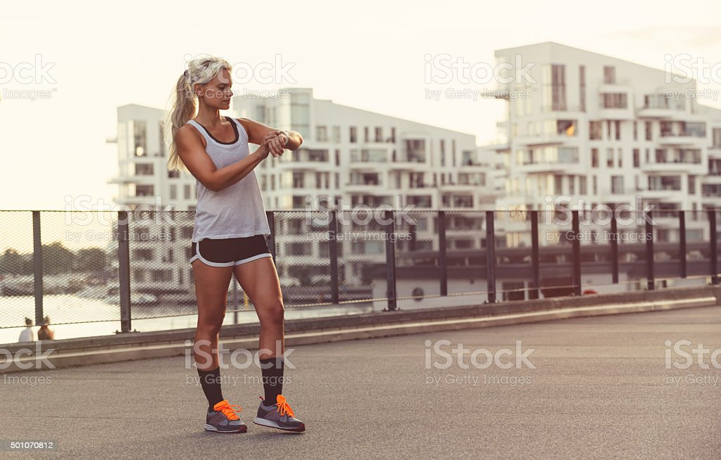 Female runner use wearable smart watch to get results stock photo