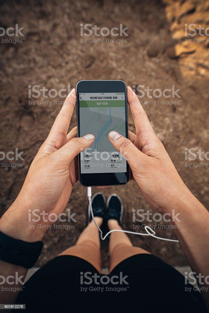 Female runner using a fitness app on her mobile phone stock photo