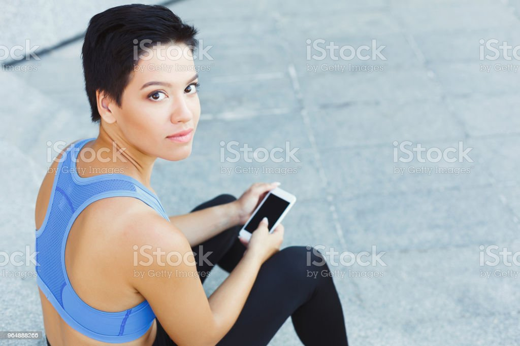 Female runner with smartphone on stairs royalty-free stock photo