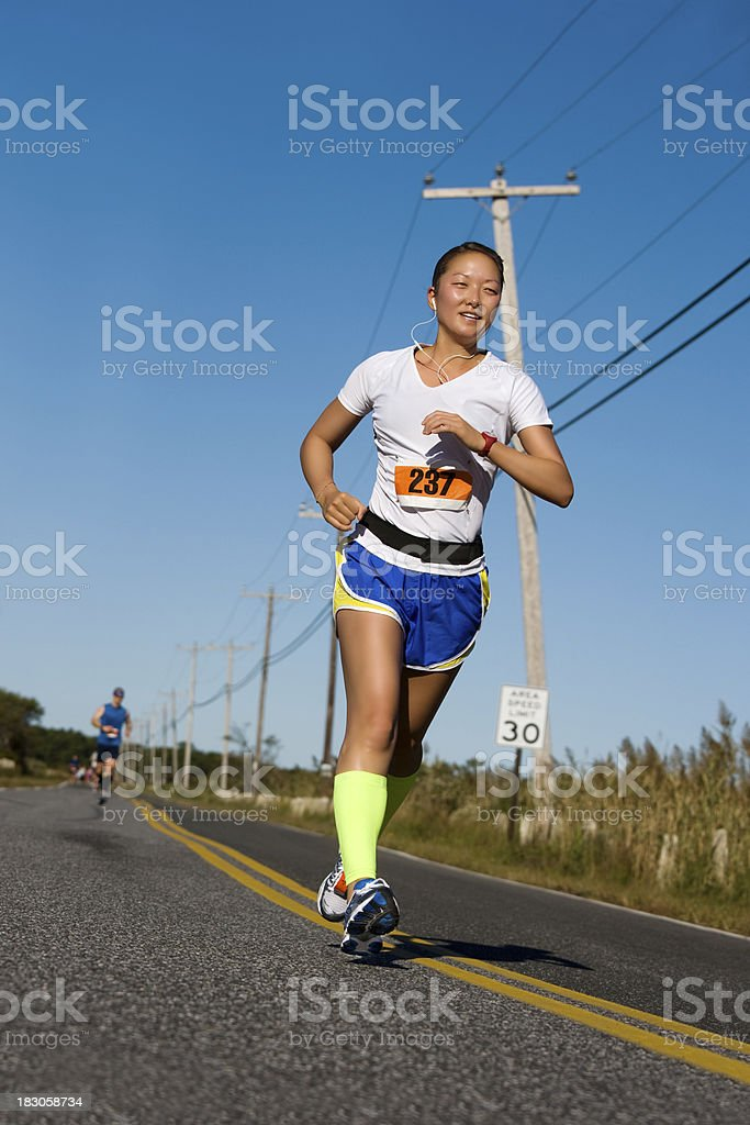 female running a race on a road wearing blue shorts royalty-free stock photo