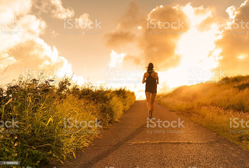 Female running at sunset. stock photo