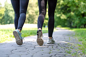 Wellness and fitness concept - low angle view of running women in the park on a sunny morning.