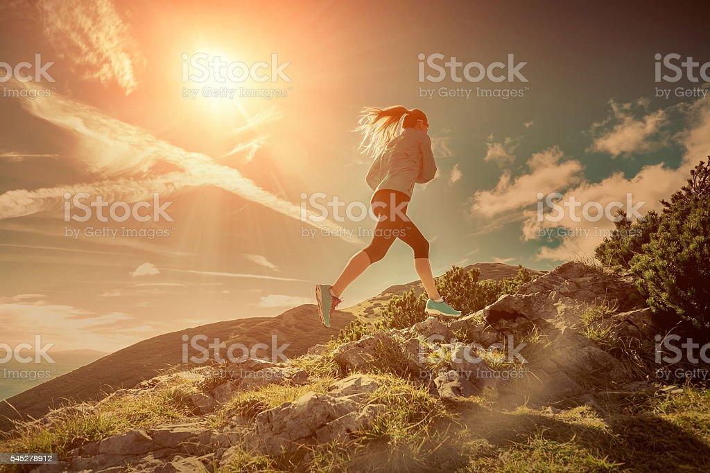 Female running in mountains under sunlight. stock photo