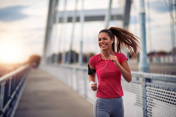 weiblich, in der stadt laufen - joggerin stock-fotos und bilder