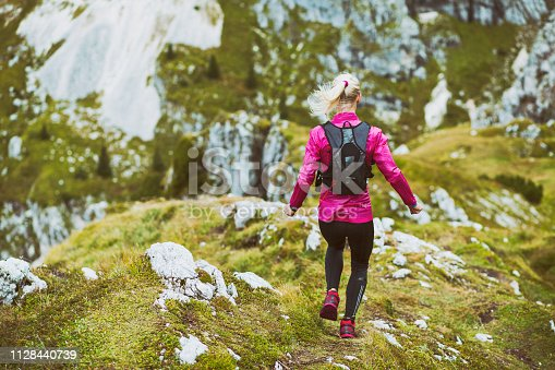 Cross country running in the high mountains. Woman with all the running equipment.