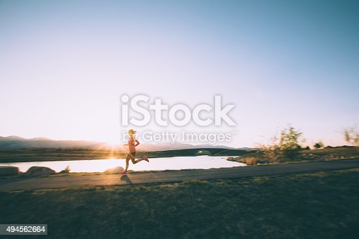 A mid-adult female runner runs along a footpath in Utah during a cool spring sunset. The sunburst pierces the pristine blue Utah sky.