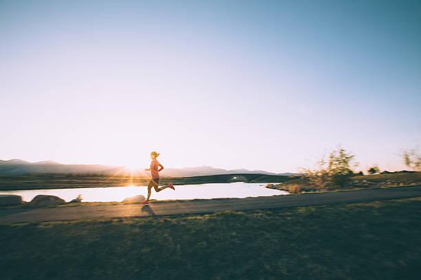 mujer corriendo en camino durante la puesta de sol en utah - estilo de vida austero fotografías e imágenes de stock