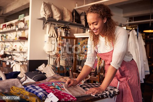 Female Sales Assistant Arranging Textiles In Homeware Store