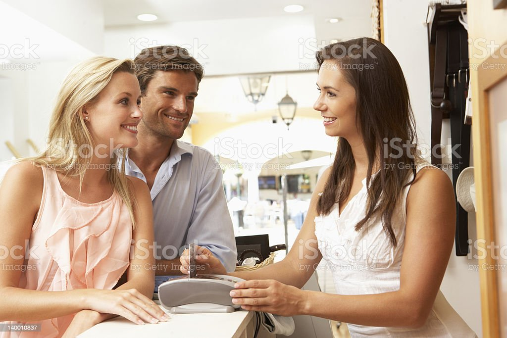 Female Sales Assistant At Checkout Of Clothing Store With Customers royalty-free stock photo