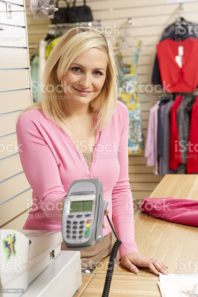 Female sales assistant in clothing store royalty-free stock photo
