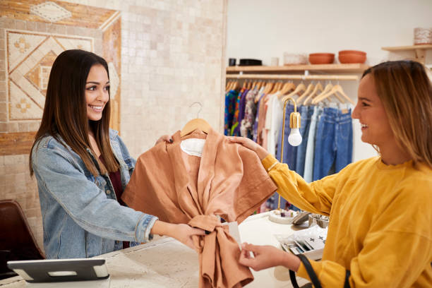 vrouwelijke sales assistant in onafhankelijke kleding en cadeauwinkel waar vrouwelijke klant - verkoopster stockfoto's en -beelden