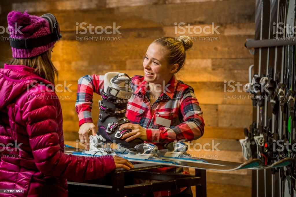 Female Sales Assistant tuning up skis for customer. stock photo