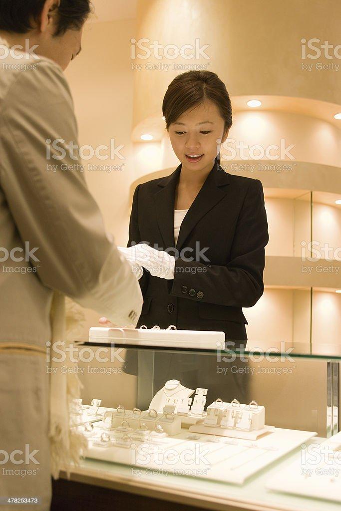 Female salesclerk taking care of customers stock photo