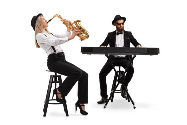 Female saxophonist and a male keyboard player Full length shot of a female saxophonist and a male keyboard player isolated on white background keyboard player stock pictures, royalty-free photos & images