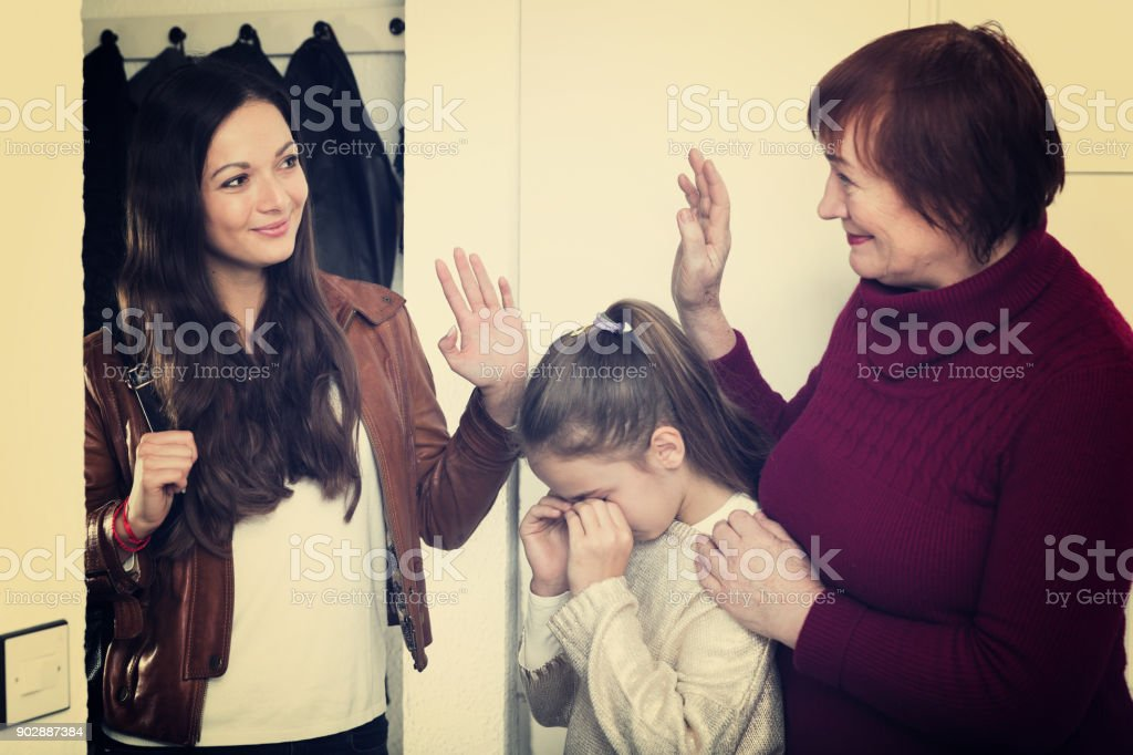 Female saying goodbye to senior woman with crying girl stock photo