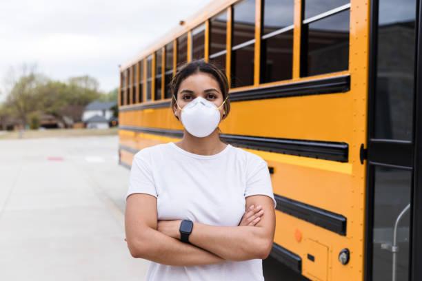 Female school bus driver wearing N95 mask stock photo