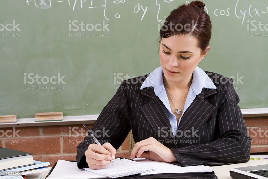 female school teacher preparing material for the class stock photo