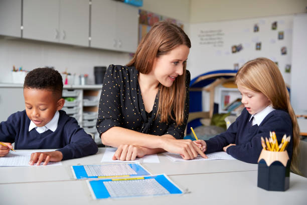Female school teacher sitting between two primary school kids at a table in a classroom, helping a girl with her work, close up Female school teacher sitting between two primary school kids at a table in a classroom, helping a girl with her work, close up between stock pictures, royalty-free photos & images