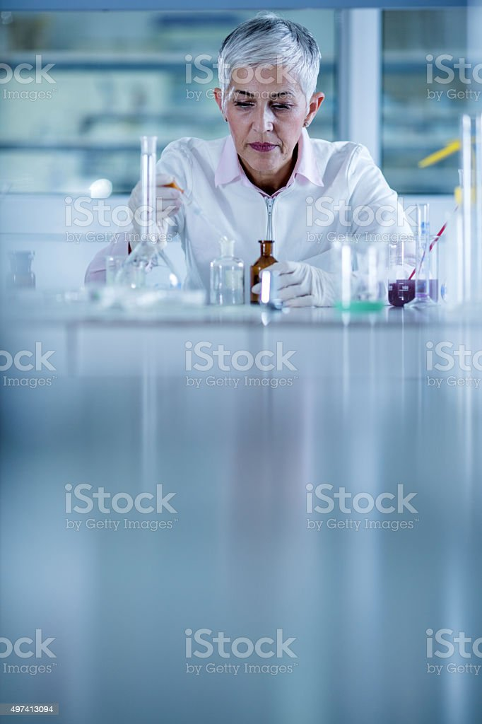 Mature chemist examining chemicals for her scientific research in...