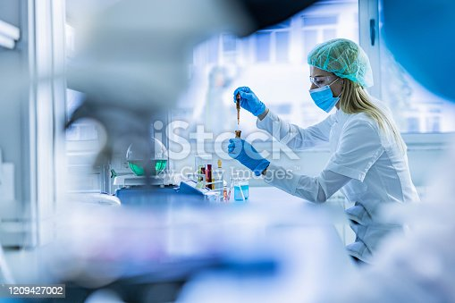 Young female chemist working with poisonous liquid in a laboratory.