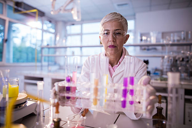 Female scientist holding large group of multi-colored test tubes. stock photo