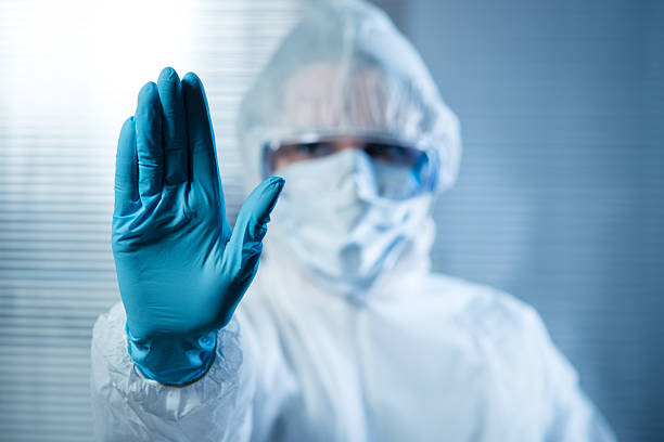 Female scientist in protective hazmat suit with hand raised Scientist with hand raised in hazmat protective suit, stop concept. decontamination stock pictures, royalty-free photos & images