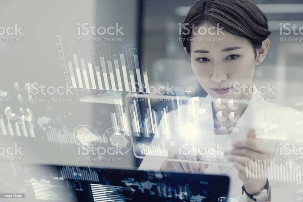 Female scientist looking futuristic GUI. stock photo