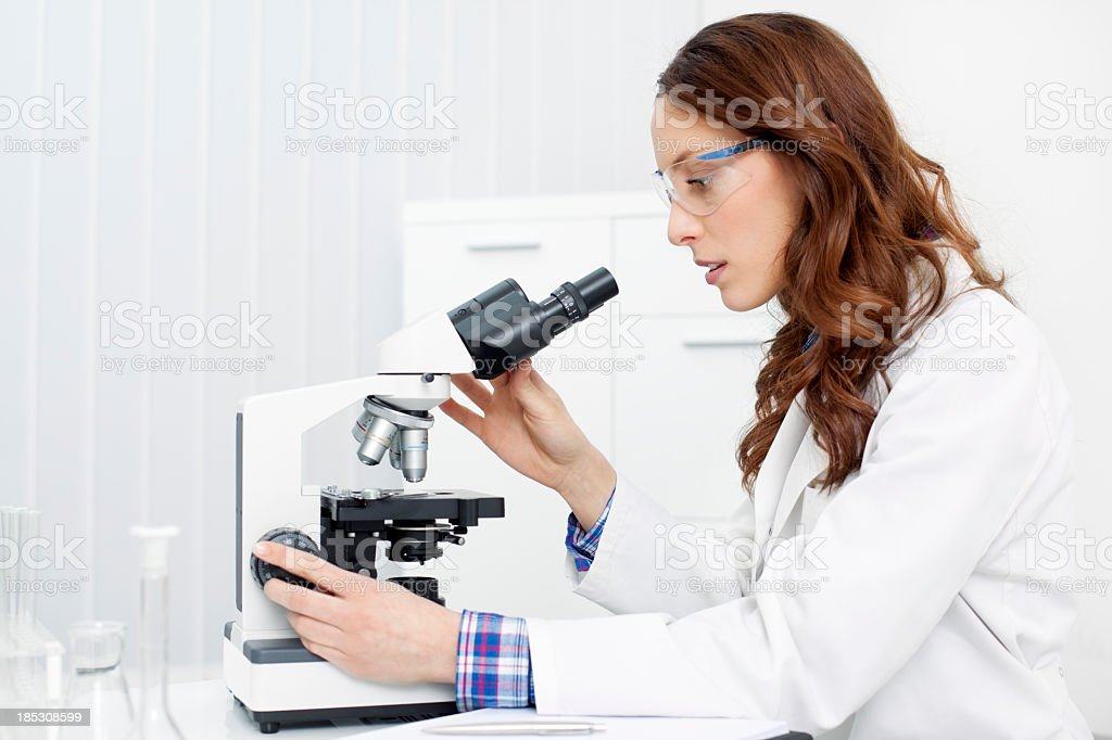 Female Scientist Looking Through a microscope stock photo
