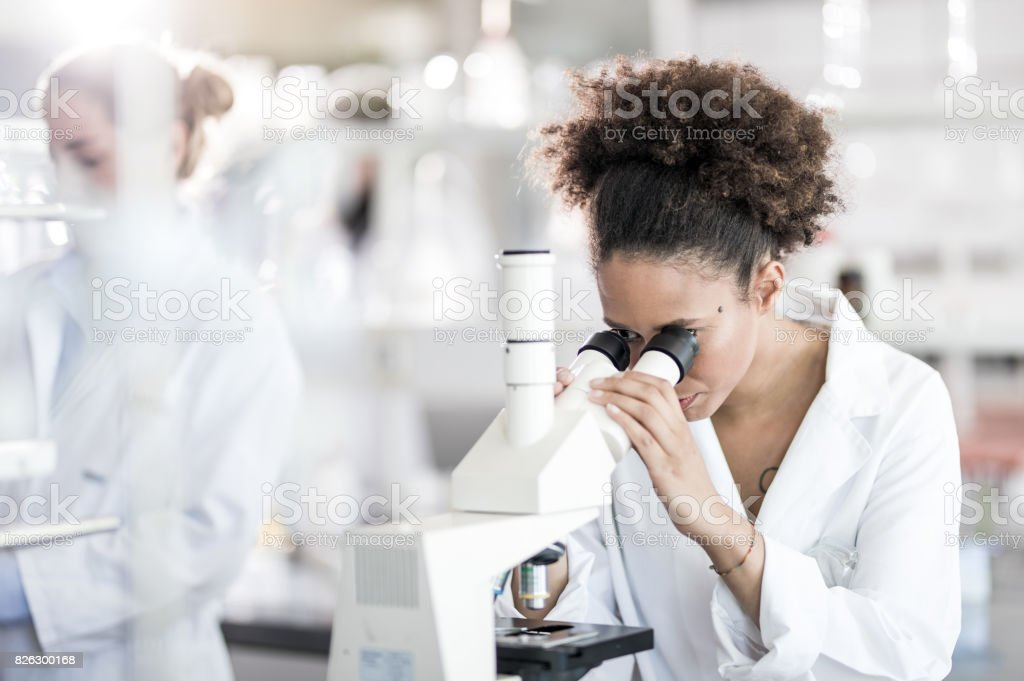 Female Scientist Looking Through Microscope stock photo
