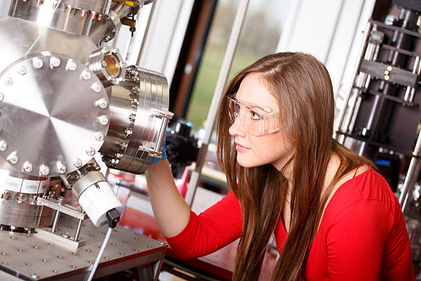 female scientist looking to the laser deposition chamber - physics stock photos and pictures