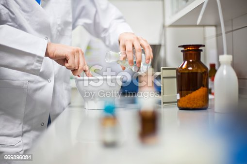 Midsection of female scientist making medicine in laboratory. Professional using mortar and pestle while pouring solution from flask. She is working at pharmacy.