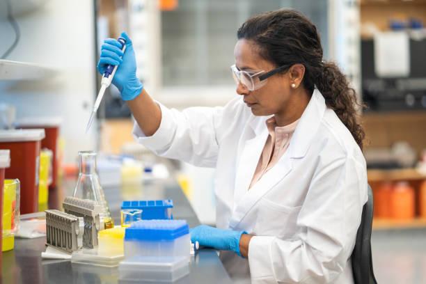 pipetting féminin de scientifique dans le laboratoire - photos de pharmacie photos et images de collection