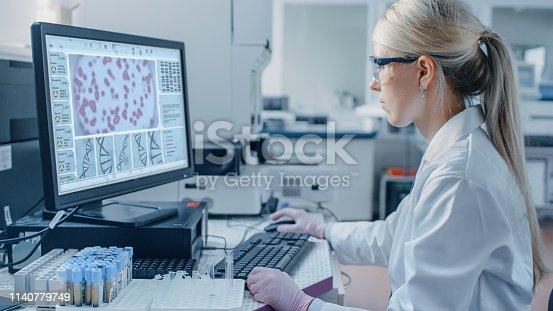 istock Female Scientist Sits at His Workplace in Laboratory, Uses Personal Computer. Screen Shows Analyze of DNA. I the Background Genetics Research Centre with Innovative Equipment. 1140779749