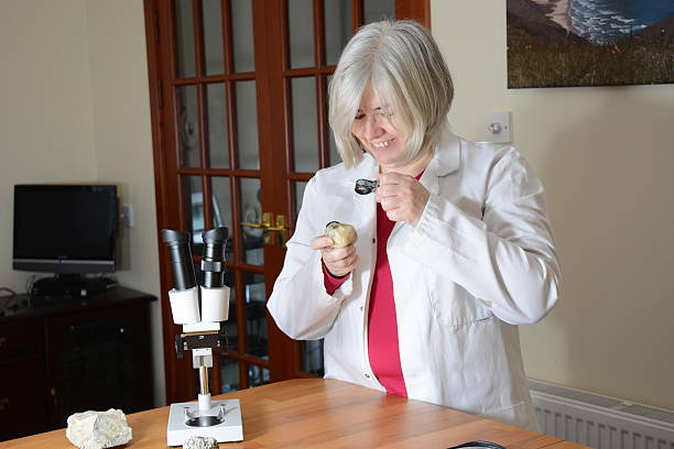 Female Scientist smiling at a rock stock photo