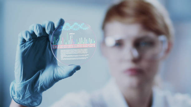 Female scientist studying DNA mutations. Holding virtual plate with data stock photo
