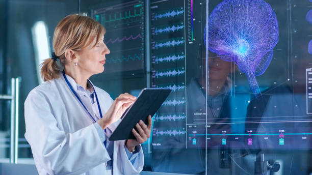 Female Scientist Uses Tablet Computer In the Modern Brain Study Laboratory and Monitors EEG Reading and Brain Model Functioning. stock photo