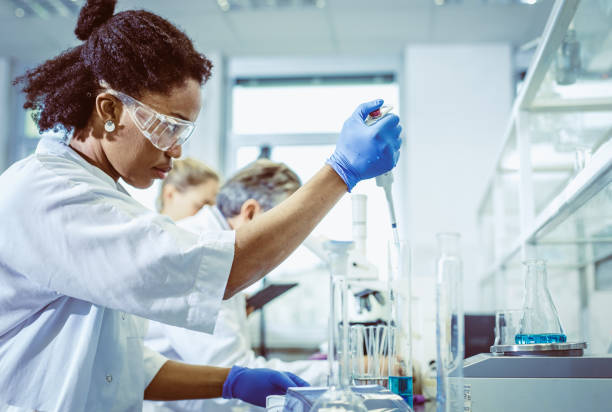 Female Scientist Using an Automatic Pipette Female Scientist Using an Automatic Pipette chemical reaction stock pictures, royalty-free photos & images