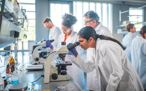 Female scientist using microscope in laboratory stock photo