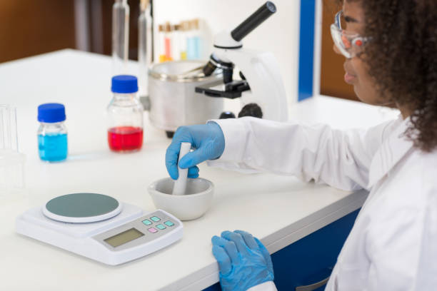 Female Scientist Using Mortar Working In Laboratory Making Chemicals Powder For Experiment, Researcher Mix Race stock photo