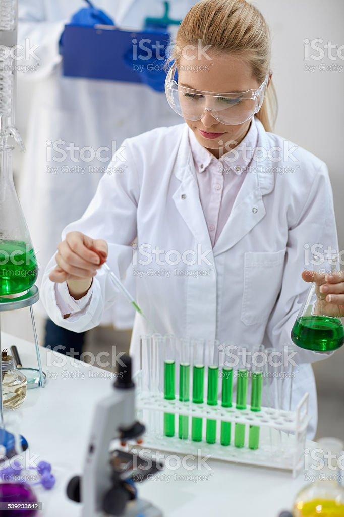 Fêmea cientista com Pipeta e os tubos Fazer teste foto royalty-free