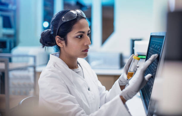 female scientist working in the lab, using computer screen - scientist imagens e fotografias de stock