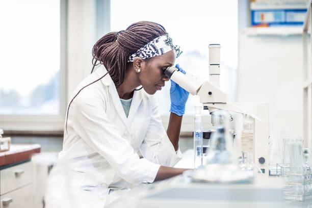 wissenschaftlerin arbeitet im labor unter dem mikroskop - krebs tumor stock-fotos und bilder